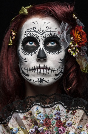 crazy girl: a woman with her face painted as a traditional day of the dead sugarskull mask Stock Photo