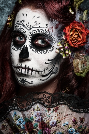 mad girl: a woman with her face painted as a traditional day of the dead sugarskull mask Stock Photo