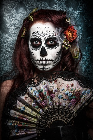 a woman with her face painted as a traditional day of the dead sugarskull mask photo