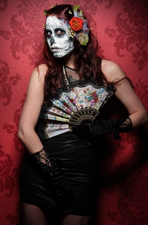 wicked: a woman with her face painted as a traditional day of the dead sugarskull mask Stock Photo