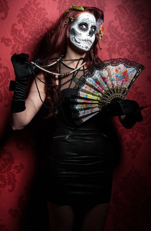 painted face mask: a woman with her face painted as a traditional day of the dead sugarskull mask Stock Photo