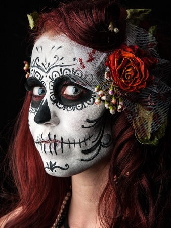 crazy woman: a woman with her face painted as a traditional day of the dead sugarskull mask Stock Photo