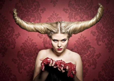 a female with a wicked demon hairstyle holding raw meat photo