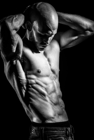 male bodybuilder: a young fit athlete posing his ripped body