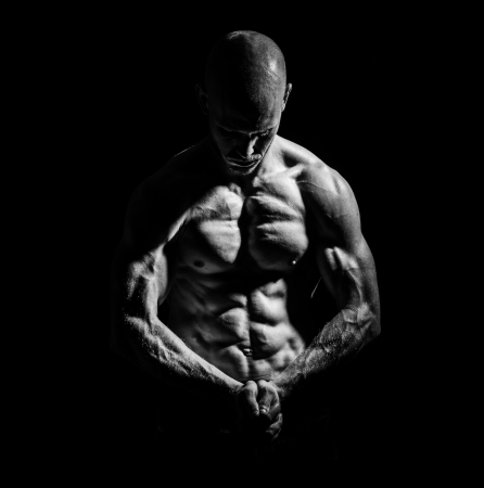 ripping: a young fit athlete posing his ripped body