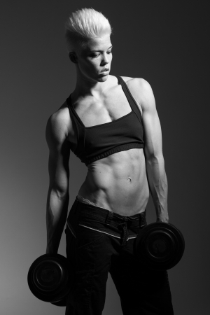 trained: a very fit woman posing her muscular body