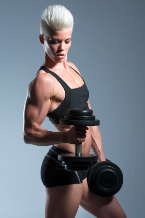 a very fit woman posing her muscular body photo