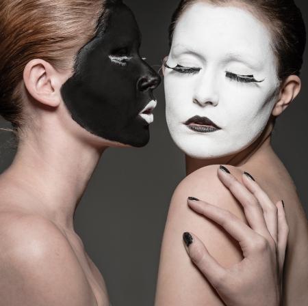 pantomima: dos chicas jóvenes con ying yang maquillaje estilo Foto de archivo