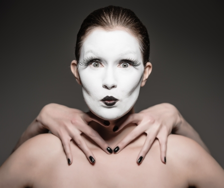 a young woman with a white face makeup photo