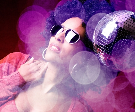 70s adult: 70s disco girl with a disco ball and a big afro hair Stock Photo