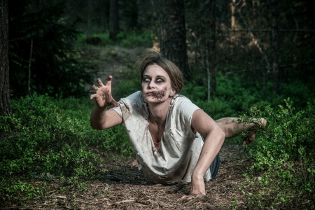 a scary undead zombie girl lying on the ground Stock Photo
