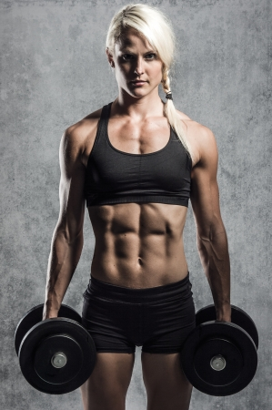 attractive female: a young and very fit woman training with dumbells