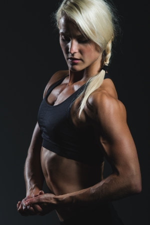 a young and very fit woman flexing her muscles