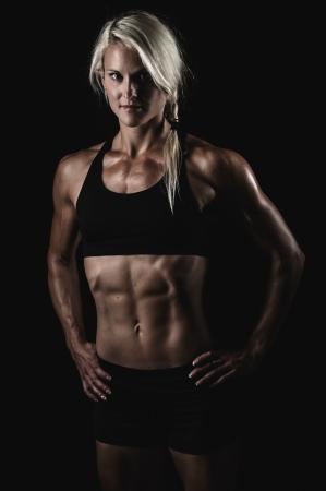 mujer deportista: una mujer joven y muy en forma flexionando sus m�sculos