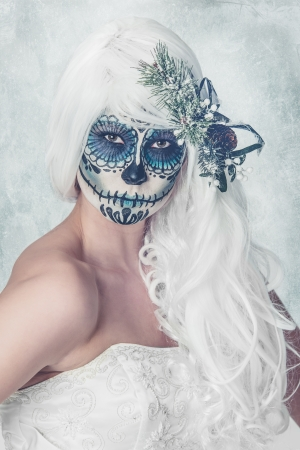 a female bride with her face painted as a traditional day of the dead sugarskull mask Stock Photo