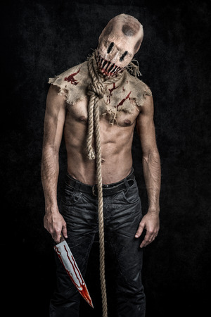 a scary looking scarecrow demon with a bloody knife Stock Photo - 33874736