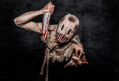 een eng uitziende vogelverschrikker demon met een bebloed mes