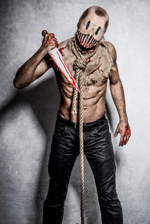 a scary looking scarecrow demon with a bloody knife
