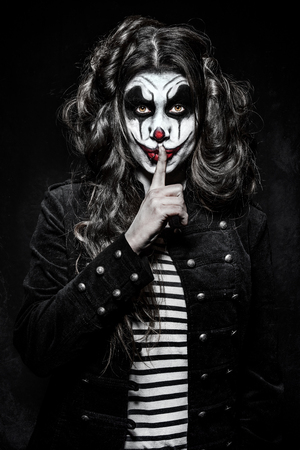 a scary evil clown girl with a wicked makeup Фото со стока