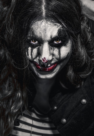 a scary evil clown girl with a wicked makeup Stock Photo