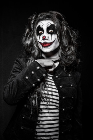 evil clown: a scary evil clown girl with a wicked makeup Stock Photo