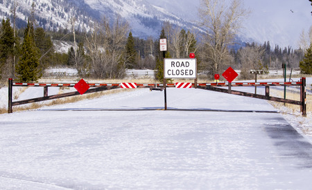 Road closed sign and gate blocking road access during winter Stock Photo