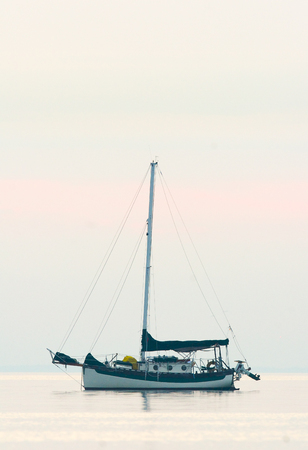 Cruising sailboat anchored out in the bay during morning Stok Fotoğraf