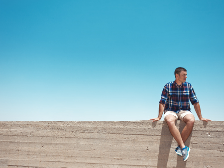Man sitting on cement wall at sunny day