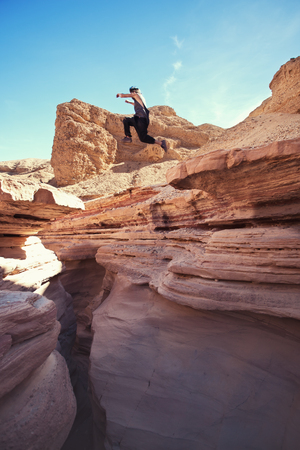 brave man jumping over the cliff in canyon, and little motion blur Stock Photo