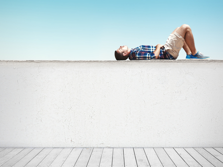 Man lying horizontal on cement wall at sunny day Stock Photo