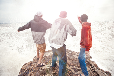 three brave men standing on a cliff in storm