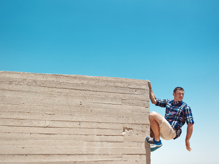 Man hanging on cement wall at sunny day Stock Photo