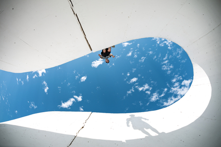 brave extreme man with big shadow silhouette preparing for the jump over the gap between concrete walls