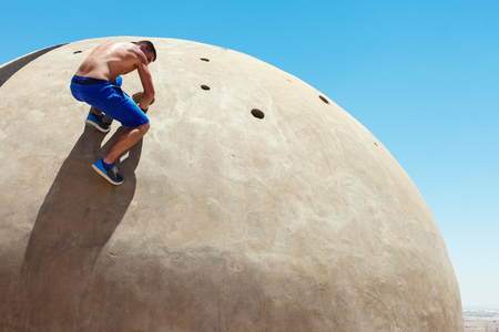 Athletic man climbing concrete wall at sunny day Stock Photo