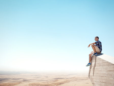 Young man sitting on a cliff and looking at the desert
