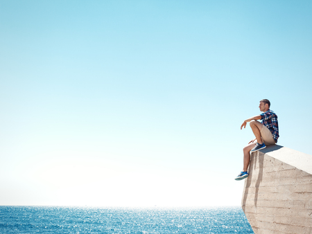 Young man sitting on a cliff and looking at the sea
