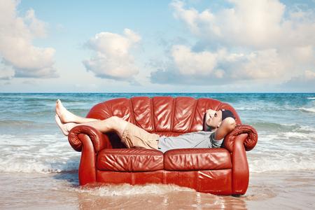 ビーチで革のソファで休んでいる男