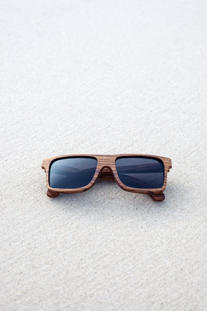 wooden sunglasses lying on the white sand Stock Photo