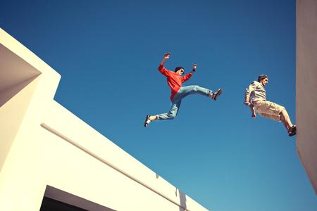 지붕 위에서 뛰어 오르는 두 용감한 남자, 그리고 작은 동작 흐림 스톡 콘텐츠