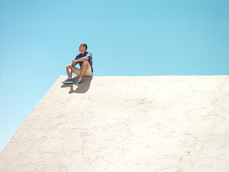 Young man sitting on a wall at sunny day Stock Photo