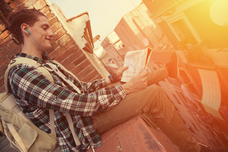 Young and brave man with backpack sitting on the edge of high roof with map in hands Stock Photo