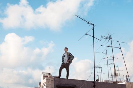 若くて勇敢な旅の男を屋根の上に立っている笑顔、明るく青い空と白い雲アンテナと遠くを見て