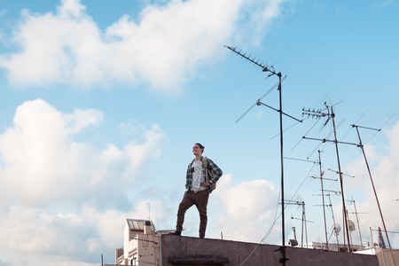 Young and brave traveling man standing on the roof, smiling and looking far away with bright blue sky and white clouds and antennas Stock Photo