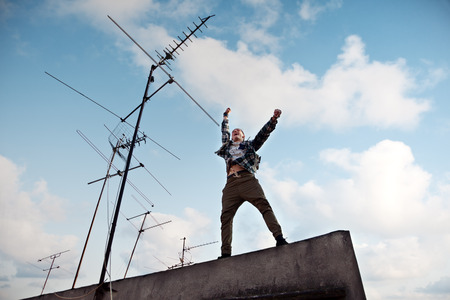 Happy young man jumping on the rooftop with bright blue sky and white clouds at background
