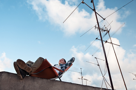 Cheerful and smiling young man resting in the chair at the edge of the roof in the city Stock Photo