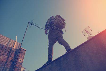 勇敢な旅行者の都市の高い屋根の上を歩く 写真素材
