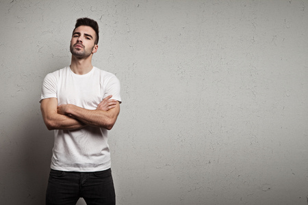 Handsome man wearing white blank t-shirt with white grunge wall on background