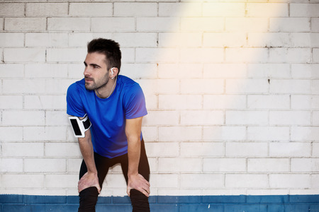 tired male athlete with earphones resting near brick white wall with sun light