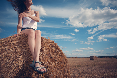Young and handsome girl sitting outdoors on haystack and smiling