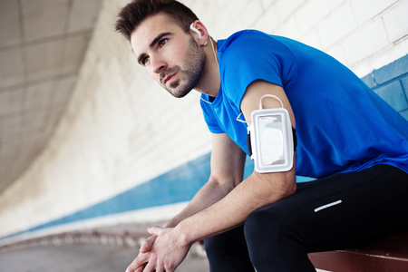 portrait of athlete listening music with smartphone and armband sitting on bench Standard-Bild